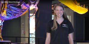 Gülümseyen bir kadın bir T. rex fosil sergisinin önünde duruyor